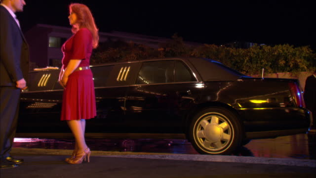 MEDIUM ANGLE ZOOM IN OF WOMEN EXITING A LIMO FROM SIDE. WOMEN ARE WEARING HIGH HEELS SHORT SKIRTS AND DRESSY CLOTHES.