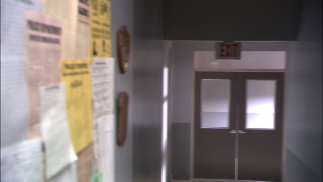 "close angle of bulletin board covered with flyers. one flyer reads ""wanted by fbi"" and features fingerprints and mug shot photos of criminals. - police station stock videos & royalty-free footage"