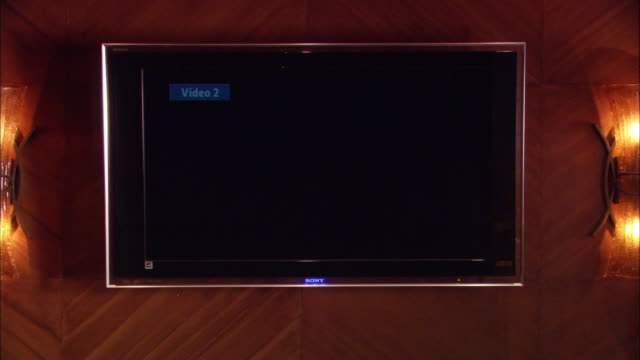 "CLOSE ANGLE OF LARGE FLAT SCREEN ""SONY"" TELEVISION ATTACHED TO WALL. COULD BE USED FOR ANY ROOM IN A HOME OR APARTMENT. WALL LAMPS ARE ON BOTH SIDES OF TV. ELECTRONICS."