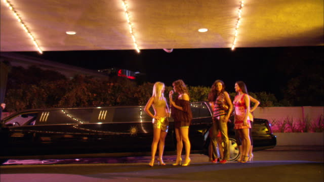 WIDE ANGLE ZOOM IN OF WOMEN WALKING FROM LIMO TO BUILDING. WOMEN ARE WEARING HIGH HEELS SHORT SKIRTS AND DRESSY CLOTHES.