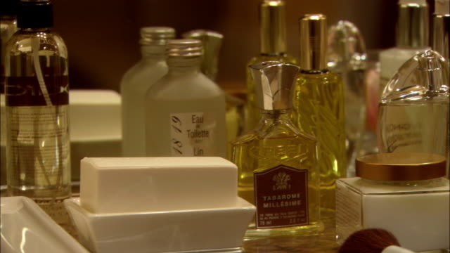 close angle of assortment of perfumes, fragrances, or colognes on counter in front of mirror. - parfum stock-videos und b-roll-filmmaterial