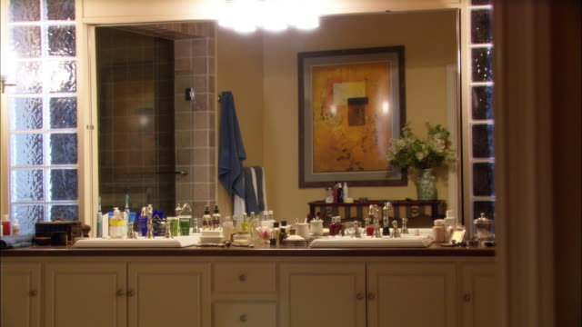 medium angle of bathroom counter top and mirror. large assortment of bottles, containers, perfume, cologne, other toiletries. - bathroom stock videos and b-roll footage