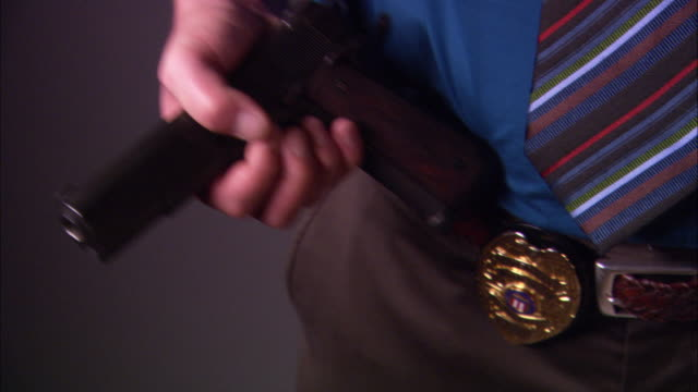 close angle series of police officer pulling a gun from his back pocket to hold in his hand. man's badge is attached to his belt. weapons. - gun belt stock videos and b-roll footage