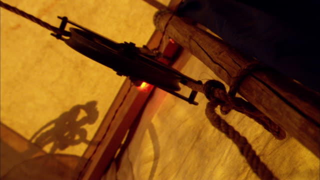 up angle of pulley inside canvas tent. rope is tied to wood tent frame pole. hand reaches in frame and unhooks rope causing it to rapidly unwind from pulley. pulley wheel spins. - flaschenzug stock-videos und b-roll-filmmaterial