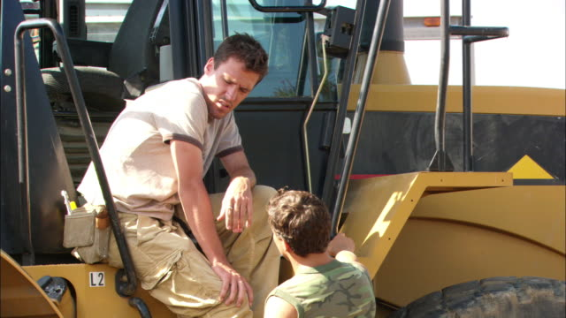 medium angle of construction workers talking. one man is sitting on bulldozer talking to man standing. could be taking a break. man wearing tool belt and workpants. could be construction site. - tool belt stock videos and b-roll footage