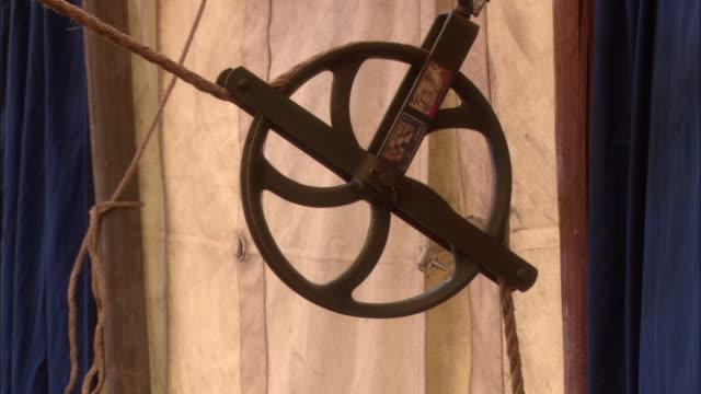 vídeos de stock, filmes e b-roll de medium angle of rope on rusty pulley inside canvas tent. could be circus tent or carnival tent. rope pulls out of pulley and off-screen as if cut. pulley wheel spins as rope pulls free. could be accident. - roldana