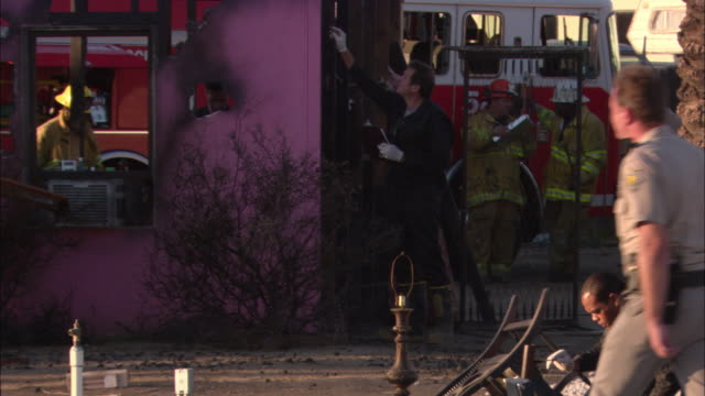 WIDE ANGLE OF AFTERMATH OF HOUSE FIRE. INVESTIGATOR WITH CLIPBOARD EXAMINES SIDE OF BURNED PINK STUCCO HOUSE.