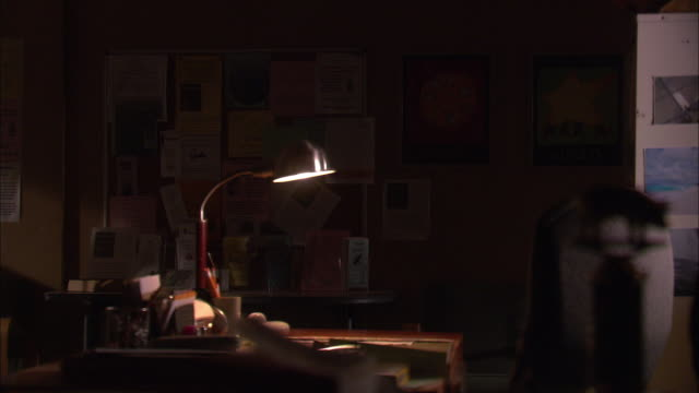 medium angle of dark office. single desk lamp illuminates desk in center of room. bulletin board in bg has several flyers posted. - notice board stock videos and b-roll footage
