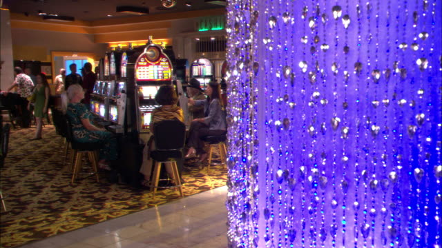wide angle of casino lobby. women gamble at slot machines. glass or crystal bead decoration hangs from ceiling to floor on right. - casino floor stock videos & royalty-free footage