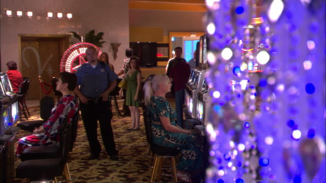 wide angle of casino lobby. security guards walk down aisle of women gambling at slot machines. men and women gamble at tables in bg. - guardia di sicurezza video stock e b–roll