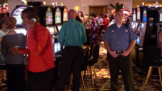 WIDE ANGLE OF CASINO LOBBY. MEN AND WOMEN GAMBLE AT SLOT MACHINES AND TABLES. SECURITY GUARDS STANDS IN MIDDLE OF LOBBY.