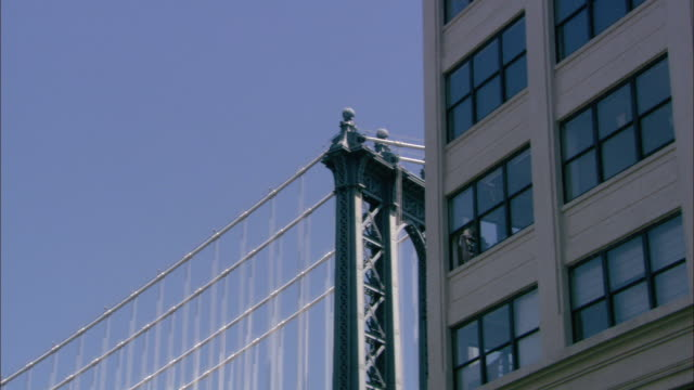 up angle of a window washer hanging out of a multi-story building, probably an office building or commercial building.  the manhattan bridge in the background. - window washer stock videos & royalty-free footage