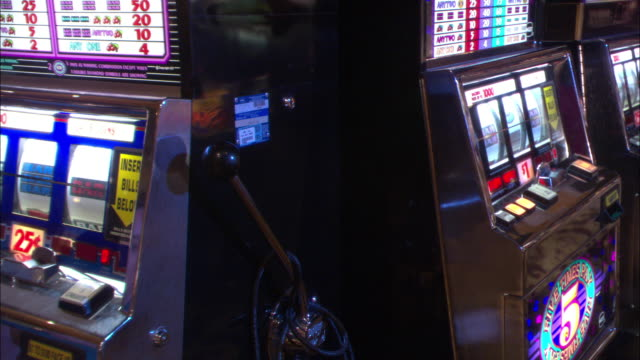 close angle of slot machines in casino. pov focuses on slot machine handle. gambling. - casino interior stock videos & royalty-free footage