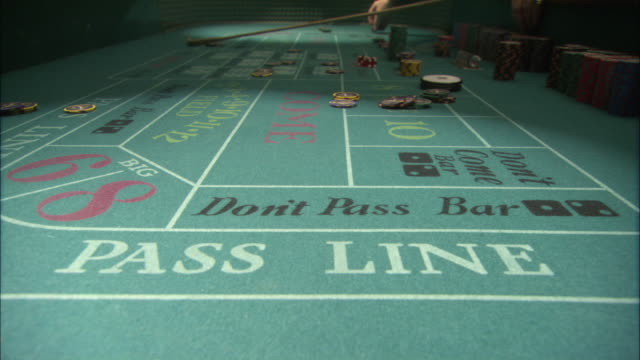 close angle of craps table from low pov. several poker chips have been placed on the board for various bets. shooter on opposite end of table rolls dice several times. - craps stock videos & royalty-free footage