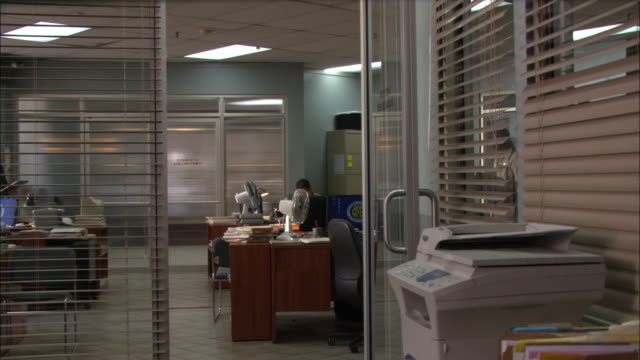 medium angle of police station offices. police officers stand and sit working at their desks in bg. copy printer fax machine visible to right. men. - fax machine stock videos & royalty-free footage