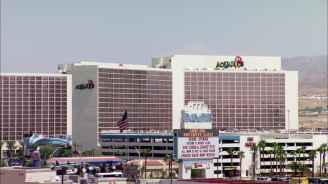 pan right to left from multi-story edgewater resort casino and parking lot with parked cars and palm trees - building storey stock videos and b-roll footage