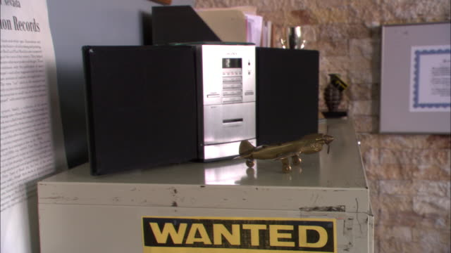 CLOSE ANGLE OF POLICE OFFICER'S OFFICE. 'POLICE DIVISION RECORDS' AND 'WANTED' SIGNS VISIBLE ON WALL AND FILE CABINET.