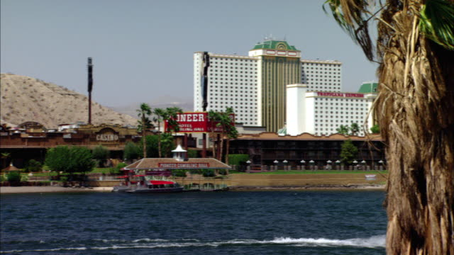 pan right to left of boats on colorado river and laughlin strip on river bank. riverboat-themed colorado belle hotel casino - casino floor stock videos & royalty-free footage