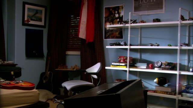 vídeos de stock e filmes b-roll de medium angle of bedroom. shelves display a clock football figurines and books. american flag hangs next to window curtains. - prateleira objeto manufaturado