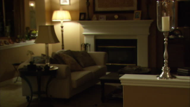 medium angle of living room. coffee table couch and end tables visible in middle of room. standing lamp is turned on next to fireplace in bg. - coffee table stock videos & royalty-free footage