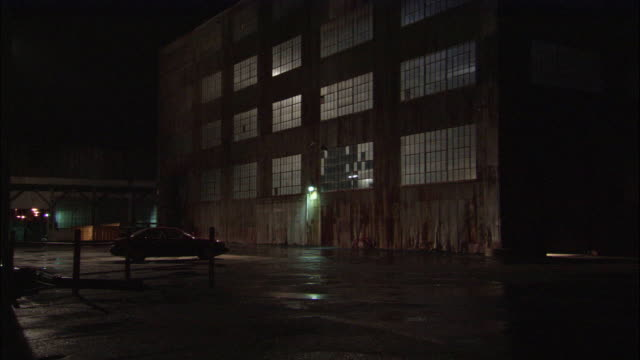 wide angle side and corner of large industrial building. may be warehouse, factory, or hangar. three or more stories high. - hangar stock-videos und b-roll-filmmaterial