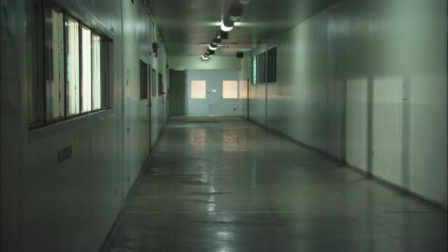vídeos de stock e filmes b-roll de wide angle of hallway in jail or mental institution or similar. fluorescent lights, linoleum floor, white walls. small windows along walls. - preso