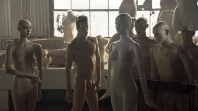 wide angle of mannequins in warehouse or factory. male and female mannequins stand in fg. mannequin parts stand or lay on wood shelf in bg. large windows in bg. - mannequin stock videos & royalty-free footage
