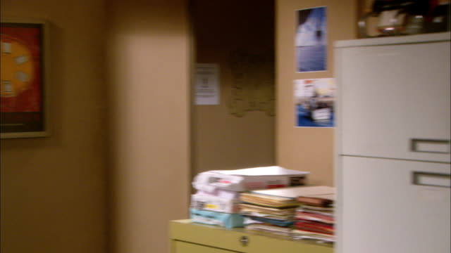 medium angle of office corner. piles of printer paper and files are stacked on file cabinet. pictures of boats visible on wall to right. poster art work visible on wall to left. - filing cabinet stock videos & royalty-free footage