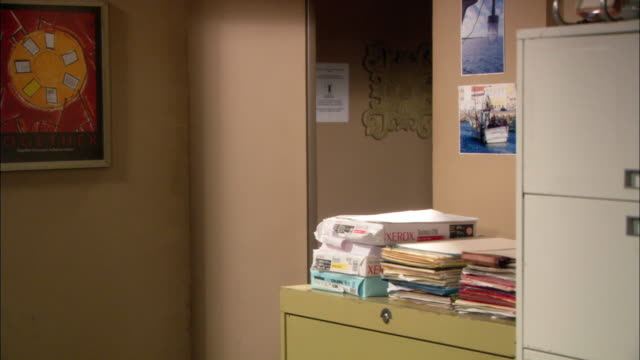vídeos de stock e filmes b-roll de medium angle of office corner. piles of printer paper and files are stacked on file cabinet. pictures of boats visible on wall to right. poster art work visible on wall to left. - portadas