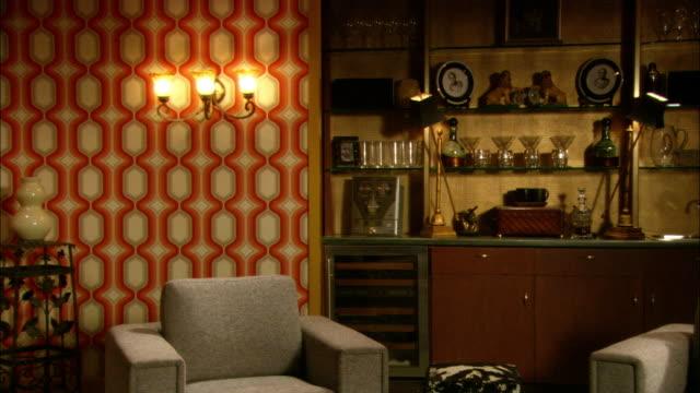 medium angle of bar on wall in hotel room or house. shelving bar unit holds liquor bottles and drinking glasses. - liten bildbanksvideor och videomaterial från bakom kulisserna