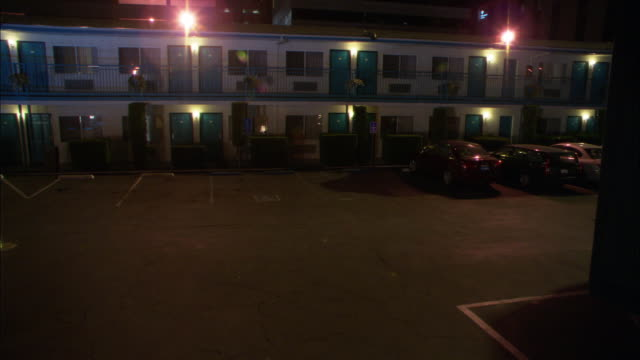 wide angle of two story motel or hotel. cars are parked in motel parking lot directly outside of rooms. room front doors and windows are visible. - motel stock videos & royalty-free footage