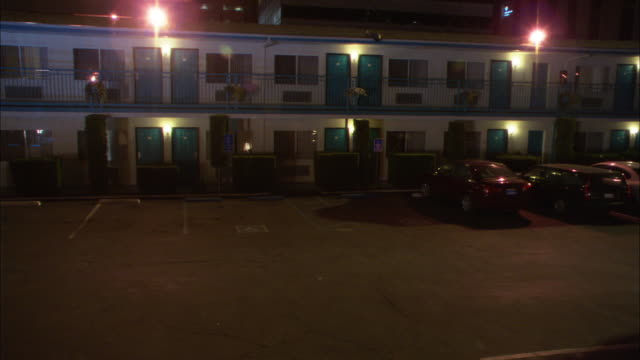 pull back wide angle of two story motel or hotel. cars are parked in motel parking lot directly outside of rooms. room front doors and windows are visible. - motel stock videos and b-roll footage