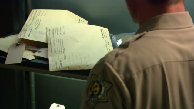 medium angle of police officer standing next to shelves filled with envelops. officer takes one envelope and places it on nearby desk with phone. envelopes could contain evidence or personal property for people in jail. men. - police station stock videos & royalty-free footage