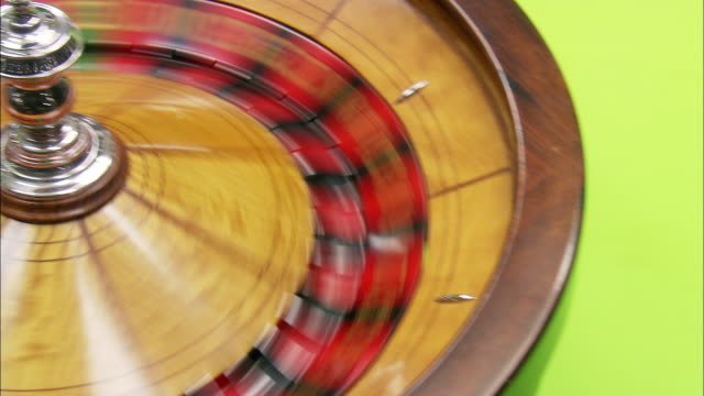 close angle of spinning roulette wheel. camera pans left across wheel as ball bounces.  gambling. green or blue screen visible. - roulette wheel stock videos and b-roll footage