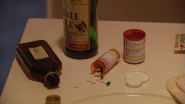 HAND HELD CLOSE ANGLE OF AN APPARENT SUICIDE SCENE. PILLS FROM OPEN BOTTLES STREWN ON SINK ALONG WITH OPEN ALCOHOL BOTTLES.