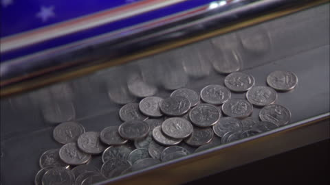 close angle of quarters falling on the bottom of a slot machine.  winning gambling at a casino. the camera zooms in on the quarters. - luck stock videos & royalty-free footage