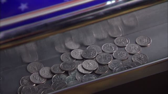 vídeos de stock e filmes b-roll de close angle of quarters falling on the bottom of a slot machine.  winning gambling at a casino. the camera zooms in on the quarters. - jogos de azar