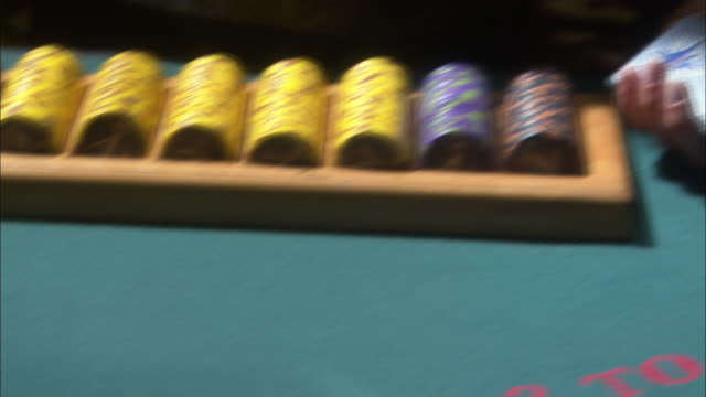 close angle of blackjack table. pov focuses on woman dealing cards. player wins with twenty one and is paid casino chips. gambling. - blackjack video stock e b–roll