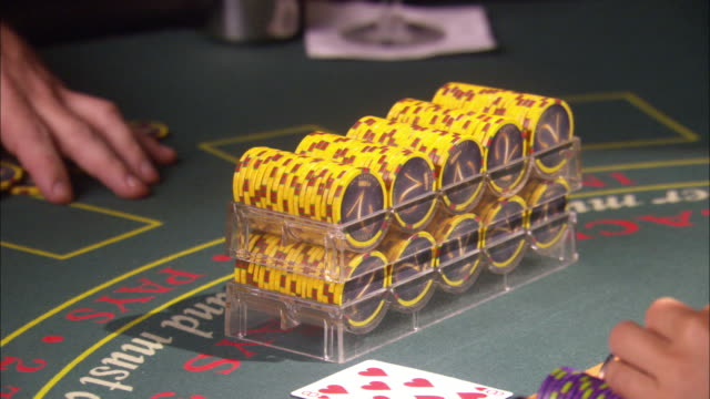 close angle of casino chips in trays passed back and forth from dealer to player. trays add to pile of chip winnings already in front of player. - gambling chip stock videos & royalty-free footage