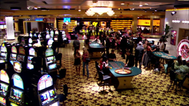 wide angle of casino interior with men and women walking about, gambling, and talking. slot machines, craps tables, roulette wheels all present. bar in background. - casino interior stock videos & royalty-free footage