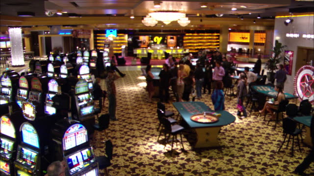 wide angle of casino interior with men and women walking about, gambling, and talking. slot machines, craps tables, roulette wheels all present. bar in background. - casino stock videos & royalty-free footage
