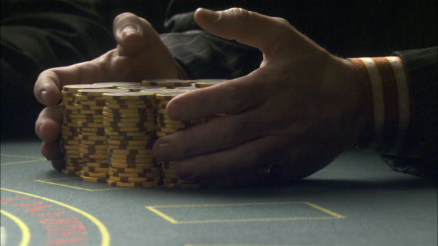 close angle of casino chips on blackjack table. man's hands run through a pile of casino chips.  gambling. hands. money. - blackjack video stock e b–roll