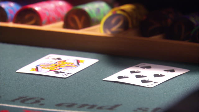 close angle of casino dealer at blackjack table. cards are dealt to players and casino chips are exchanged between dealer and players each hand. gambling. - blackjack stock videos and b-roll footage