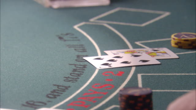 close angle of blackjack table. cards are dealt to players and casino chips are exchanged between dealer and players each hand. gambling. - blackjack stock videos and b-roll footage