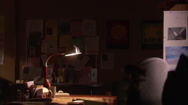 MEDIUM ANGLE OF DARK OFFICE. SINGLE DESK LAMP ILLUMINATES DESK IN CENTER OF ROOM. BULLETIN BOARD IN BG HAS SEVERAL FLYERS POSTED.