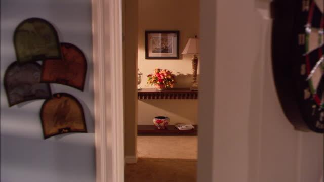 hand held medium angle of bedroom. pov pans over doorway to wall and then hallway. dartboard hangs on back of door. - bedroom doorway stock videos & royalty-free footage
