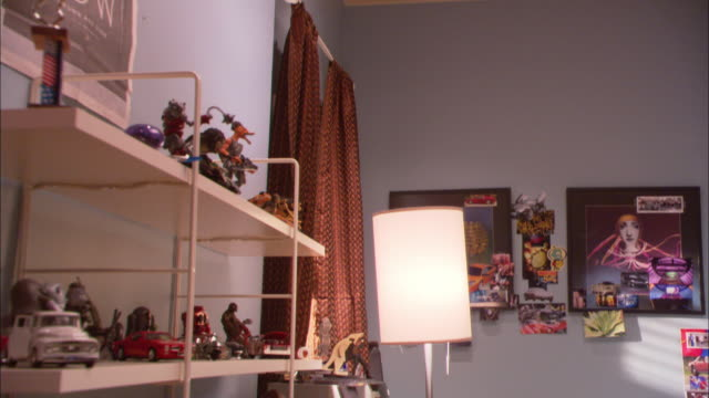 HAND HELD MEDIUM ANGLE OF TEENAGERS BEDROOM. ACTION FIGURES ARE DISPLAYED ON SHELVES. FRAMED ARTWORK AND POSTERS HANG ON WALL. LAMP IS TURNED ON IN CORNER.