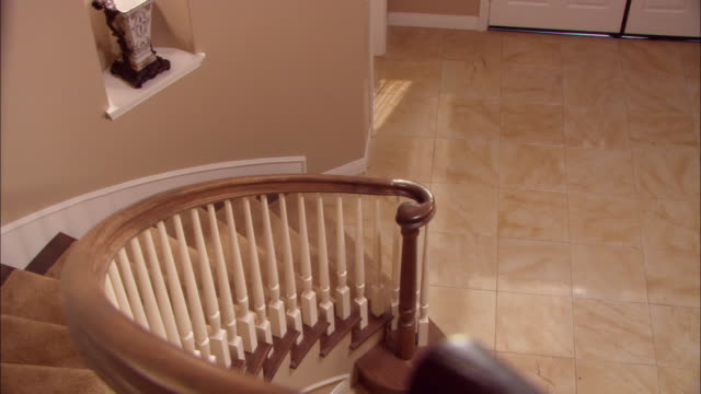 stockvideo's en b-roll-footage met medium angle down of spiral staircase. porcelain vase visible in wall opening on bottom level. upper class. foyer. - tuindeur