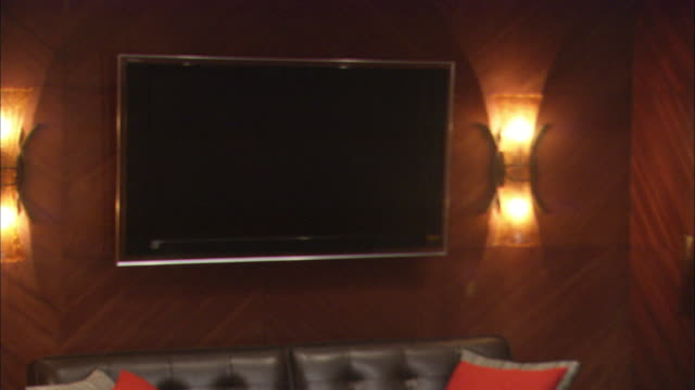 medium angle of flat screen television attached to wall. couch visible below television. wall lamps are turned on to right and left of television. - flat screen stock videos & royalty-free footage