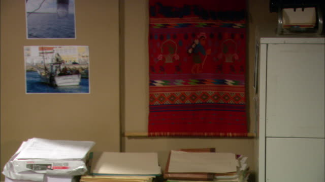 CLOSE ANGLE OF OFFICE. PILES OF PRINTER PAPER FOLDERS AND FILES LAY ON TABLE AGAINST WALL. FILE CABINET VISIBLE TO RIGHT. BOAT PICTURES AND CLOTH ART HANG ON WALL.